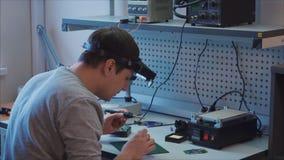 Pandown El ingeniero está soldando un componente electrónico en tablero eléctrico almacen de video