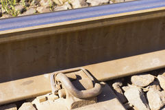Pandrol rail fasterner. A pandrol fastener holding a steel train track to the crosstie stock photography