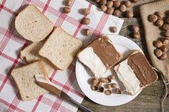 Pane affettato in piatto con la crema ed i dadi del cioccolato fotografie stock libere da diritti