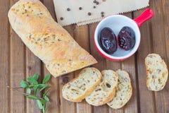 Pane affettato, prugna marinata sul piatto, pepe, foglie verdi Fotografie Stock Libere da Diritti