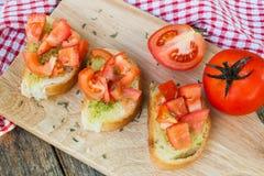 Pane all'aglio casalingo fresco con il pomodoro sul bordo di legno Fotografia Stock