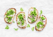Pane arrostito, formaggio a pasta molle, piselli, ravanelli e micro panini della molla di verdi Cibo sano, dimagrente, stile di v fotografie stock