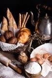 Pane, baguette, pasticceria dolce, briciole di pane con gli ingredienti di cottura e teiera fotografie stock