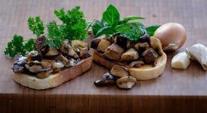Pane bianco del pane tostato con aglio, la cipolla, i funghi e le erbe fotografie stock