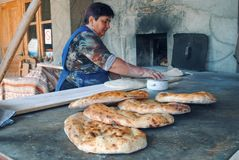 Pane bollente della donna anziana in un forno fotografia stock