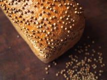 Pane con i semi di coriandolo su legno scuro Immagini Stock