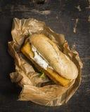 Pane con il pesce e la salsa in una carta su una vista superiore del fondo di legno fotografia stock