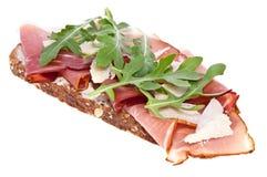 Pane con il prosciutto, l'insalata di razzo e del parmigiano Immagine Stock