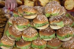 Pane croccante, hamburger, salsa al pomodoro, formaggio della mozzarella, anelli di cipolla, verdi, spruzzati con i semi di sesam Fotografia Stock Libera da Diritti
