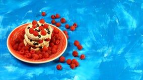 Pane croccante saporito con i lamponi delle bacche, mirtilli con panna acida, su un piatto ceramico su un fondo blu Lifesty auten immagine stock
