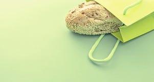 Pane crostoso fresco dell'insegna nel sacchetto della spesa su un fondo verde immagine stock libera da diritti