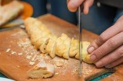 Pane dei tagli dell'uomo sul bordo con un coltello Immagini Stock Libere da Diritti