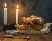 Pane del Challah su un piatto rotondo di legno sulla tavola marrone di legno fotografia stock