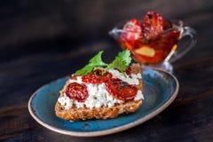 Pane del grano con la ricotta ed i pomodori seccati al sole immagine stock libera da diritti