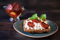 Pane del grano con la ricotta, le erbe ed i pomodori seccati al sole fotografia stock libera da diritti