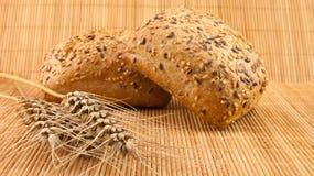 Pane di intero pasto fresco con i semi su fondo e su grano di legno Immagini Stock