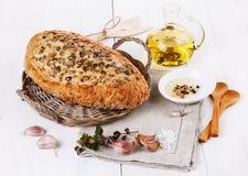 Pane di lievito naturale con i semi, l'aglio e l'olio sopra backgroun rustico Fotografia Stock Libera da Diritti