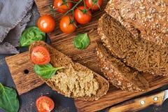Pane di segale con il pasticcio, i pomodori ciliegia e gli spinaci di fegato fotografia stock