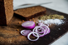 Pane e cipolle su un sale del tagliere Fotografie Stock