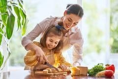 Pane e formaggio di taglio della figlia e della madre fotografia stock