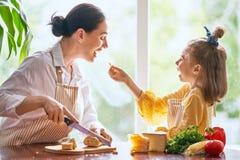 Pane e formaggio di taglio della figlia e della madre fotografia stock libera da diritti