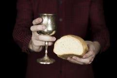 Pane e vino della tenuta dell'uomo per la comunione Fotografia Stock