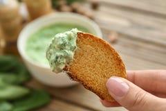 Pane femminile della tenuta della mano con la salsa degli spinaci Immagini Stock Libere da Diritti