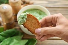 Pane femminile della tenuta della mano con la salsa degli spinaci Fotografia Stock