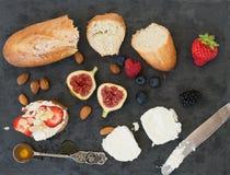 Pane, formaggio di capra, mandorla, miele e bacche su una superficie scura Fotografie Stock Libere da Diritti