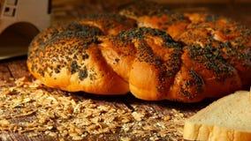Pane fragrante e una grande pagnotta con i semi di papavero che si trovano su una tavola di legno Movimento della macchina fotogr stock footage