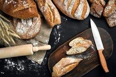Pane fresco, bordo di legno e coltello di taglio sulla tavola nera fotografia stock libera da diritti