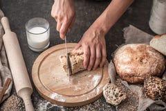 Pane fresco in primo piano delle mani su vecchio fondo di legno Immagine Stock