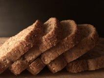 Pane integrale affettato sul tagliere di legno con fondo nero Fotografia Stock