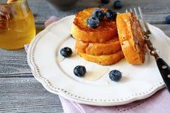 Pane inzuppato in latte/uova e zucchero e fritto in padella con i mirtilli su un piatto fotografia stock libera da diritti