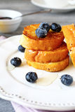 Pane inzuppato in latte/uova e zucchero e fritto in padella con i mirtilli su un piatto bianco Immagini Stock