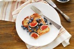 Pane inzuppato in latte/uova e zucchero e fritto in padella con la bacca fotografia stock