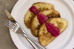 Pane inzuppato in latte/uova e zucchero e fritto in padella con la salsa del lampone immagine stock