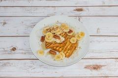 Pane inzuppato in latte/uova e zucchero e fritto in padella con le banane Immagini Stock