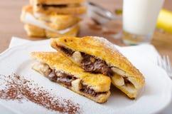 Pane inzuppato in latte/uova e zucchero e fritto in padella farcito con cioccolato e la banana Immagini Stock