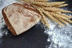 Pane italiano casalingo con le orecchie del grano e la farina sparsa su un fondo nero Immagini Stock Libere da Diritti