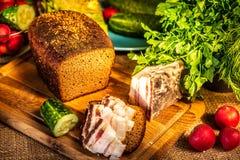 Pane, lardo e ravanello di segale su un bordo di legno nei raggi di luce solare fotografia stock libera da diritti