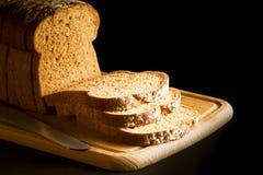 Pane nero affettato sul tagliere di legno Immagini Stock