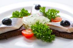Pane nero e aringa affettati su un piatto bianco Fotografia Stock