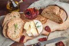 Pane o camembert inteiro do queijo processado do trigo com os tomates sol-secados com alecrins e azeite Imagens de Stock Royalty Free
