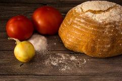 Pane, pomodori, cipolle, sale su una tavola di legno Fotografia Stock