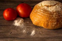 Pane, pomodori, sale su una tavola di legno Immagine Stock