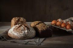 Pane quadrato rotondo e nero con insaccamento dell'uovo e fondo di legno fotografie stock