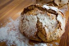 Pane rotondo sulla tavola di legno con farina intorno fotografie stock