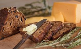 Pane scuro con i dadi ed uva passa, burro e formaggio Immagini Stock