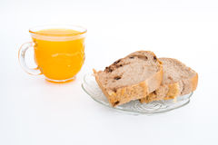Pane su un piatto e su un vetro bianchi di succo d'arancia Isolato su bianco Fotografie Stock